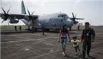 image of military family in front of military plane
